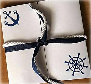 Partecipazione Matrimonio tema nautico, con cordoncino bianco e nastro di raso blu, decorato con ancora, timone, faro, rilievi di conchiglie e stelle marine all'interno 1